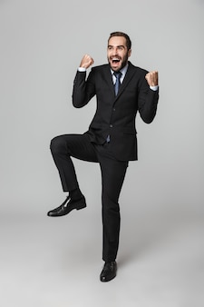 孤立した、ジャンプ、成功を祝うスーツを着て自信を持ってハンサムなビジネスマンの肖像画