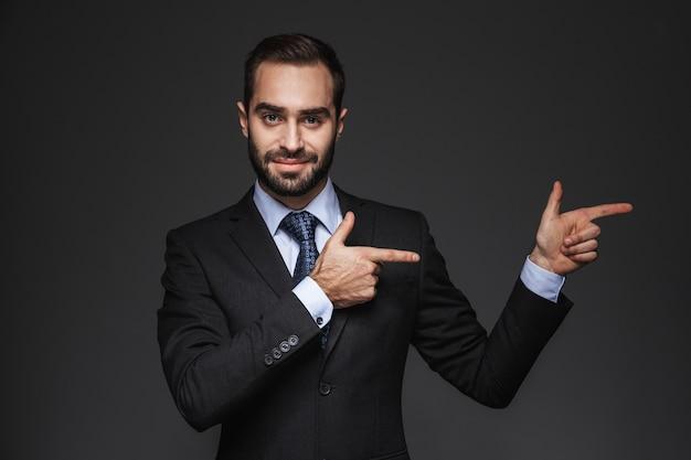 격리 된 양복을 입고 자신감 잘 생긴 사업가의 초상화, 복사 공간에서 손가락을 가리키는