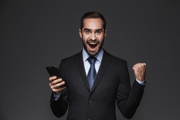 Портрет уверенного красивого бизнесмена в изолированном костюме, использующего мобильный телефон, празднует успех
