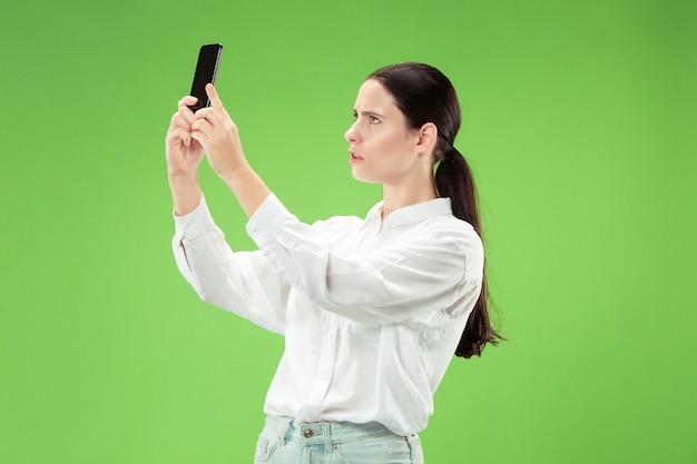 휴대 전화로 셀카 사진을 만드는 자신감이 행복 웃는 캐주얼 여자의 초상화