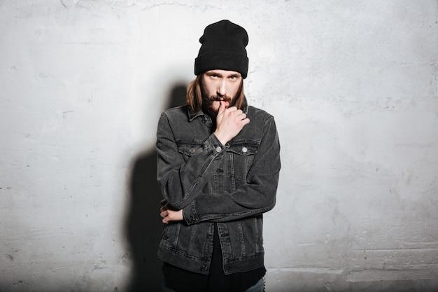 Портрет уверенного в себе хипстерского парня в шляпе, стоящего и смотрящего на фронт, изолированного на стене