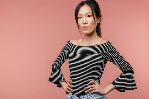 팔짱을 끼고 분홍색 벽에 고립된 채 서 있는 자신감 있는 사랑스러운 젊은 아시아 여성의 초상화