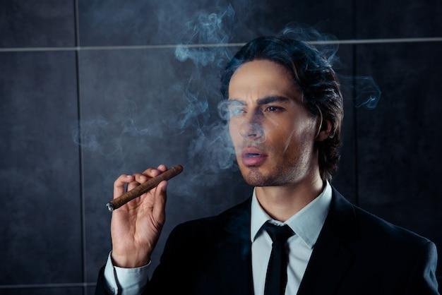Портрет уверенного в себе человека в черном костюме, курящего сигару