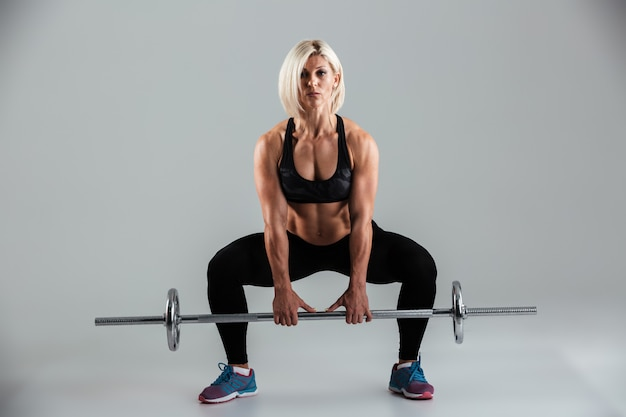 Портрет уверенной мускулистой взрослой спортсменки, делающей приседания
