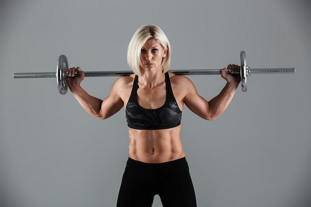 Портрет уверенно мышечной взрослой спортсменки стоя