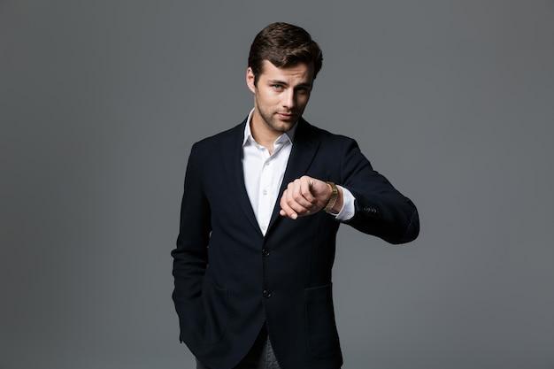 회색 벽에 고립 된 양복을 입고 자신감이 젊은 사업가의 초상화, 그의 손목 시계를보고