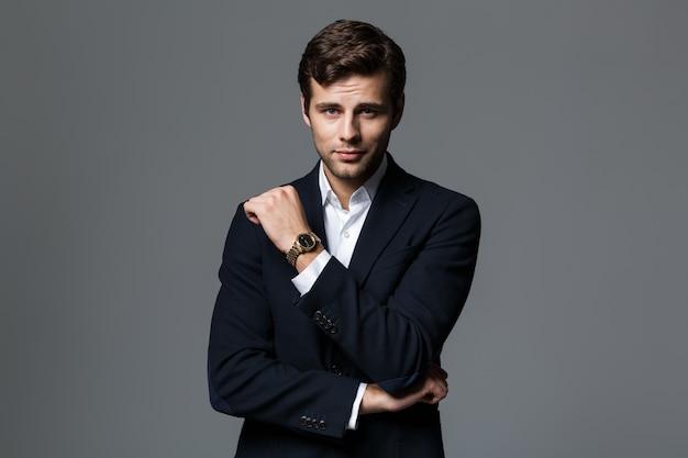 Портрет уверенного в себе молодого бизнесмена, одетого в костюм, изолированный над серой стеной