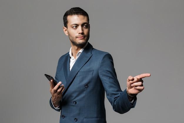 Портрет уверенного в себе молодого бизнесмена, одетого в костюм, стоящего изолированно над серой стеной, держа мобильный телефон и указывая в сторону