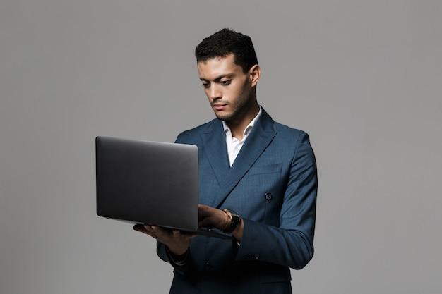 Портрет уверенно молодого бизнесмена, одетого в костюм, стоящий изолированно над серой стеной, используя ноутбук