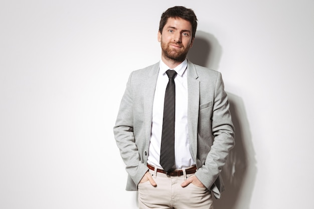 Портрет уверенного в себе молодого человека в костюме, стоя изолированном