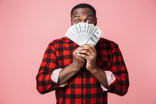 Портрет смущенного африканца в рубашке, стоящего изолированно, показывая денежные банкноты