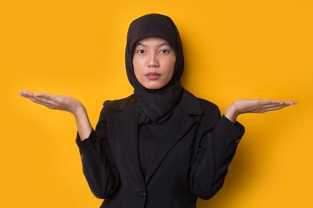 肩をすくめて混乱しているアジアのイスラム教徒の少女の肖像画