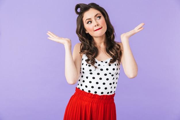 Портрет смущенной красивой девушки в стиле пин-ап с ярким макияжем, стоящей изолированно над фиолетовой стеной и пожимающей плечами