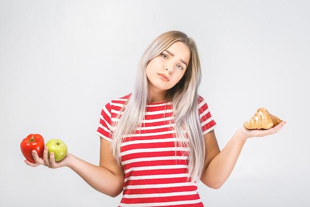 Портрет сбитой с толку красивой молодой блондинки, выбирающей между здоровой и нездоровой пищей