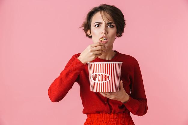 Портрет сбитой с толку красивой молодой женщины в красном платье, стоящей изолированно на розовом фоне и поедающей попкорн