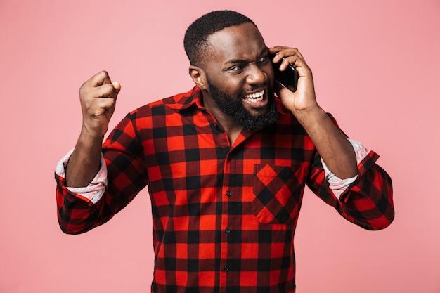 Портрет сбитого с толку случайного африканца, стоящего изолированно и разговаривающего по мобильному телефону