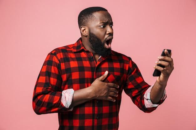 Портрет сбитого с толку случайного африканца, стоящего изолированно и использующего мобильный телефон