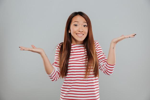 Портрет растерянной смешной девушки, пожимающей плечами