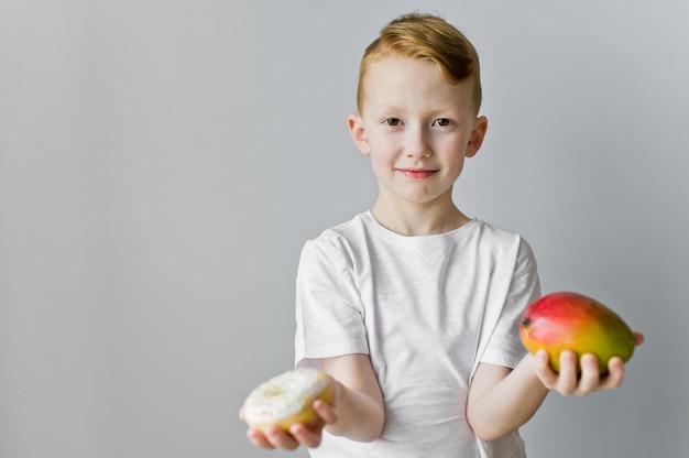 灰色の背景上ドーナツとマンゴーの間を選択する混乱の子供男の子の肖像画