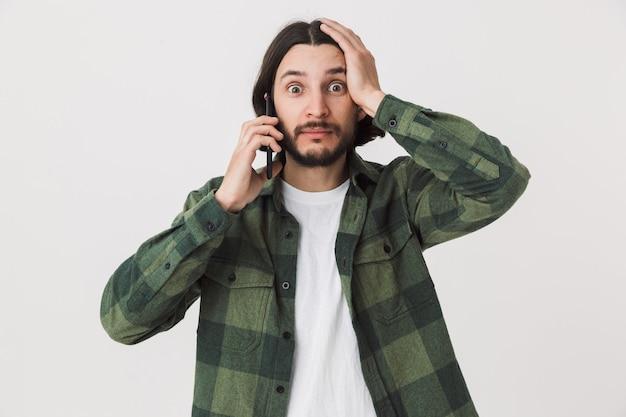 Портрет сбитого с толку молодого бородатого мужчины в повседневной одежде, стоящего изолированно над стеной и разговаривающего по мобильному телефону