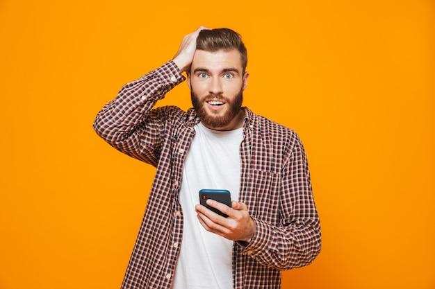 携帯電話を使用してカジュアルな服を着て混乱している若い男の肖像画