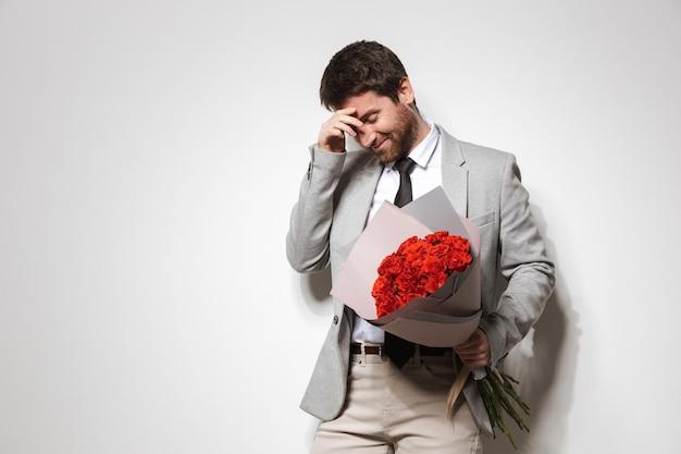 Портрет растерянного молодого человека в костюме, стоящего изолированно и держащего букет роз