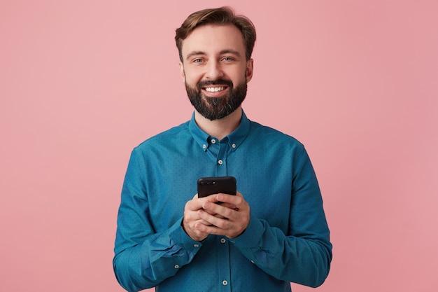 満足のいく魅力的なひげを生やした若い男の肖像画、デニムシャツを着て、彼の手でスマートフォンを持って、大きく笑って、ピンクの背景で隔離されたカメラを見ています。