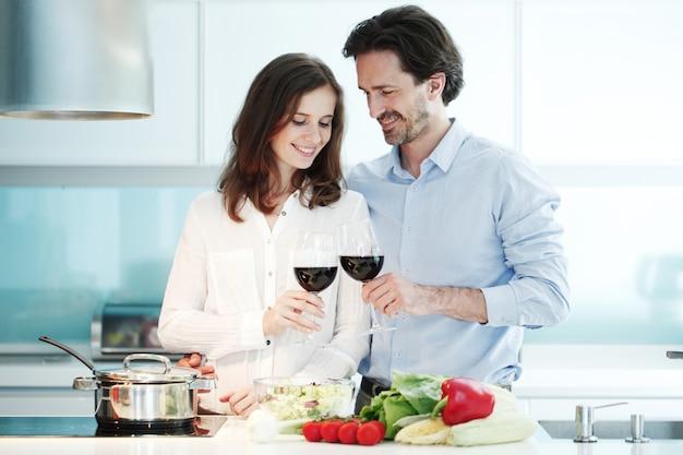 Портрет пары с бокалом красного вина во время приготовления ужина