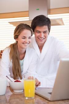 Портрет пара, завтракая при использовании ноутбука