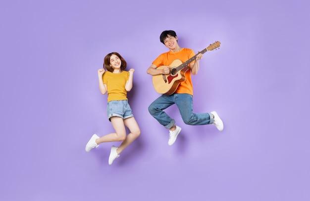Портрет пары, вскакивающей, изолированной на фиолетовом фоне
