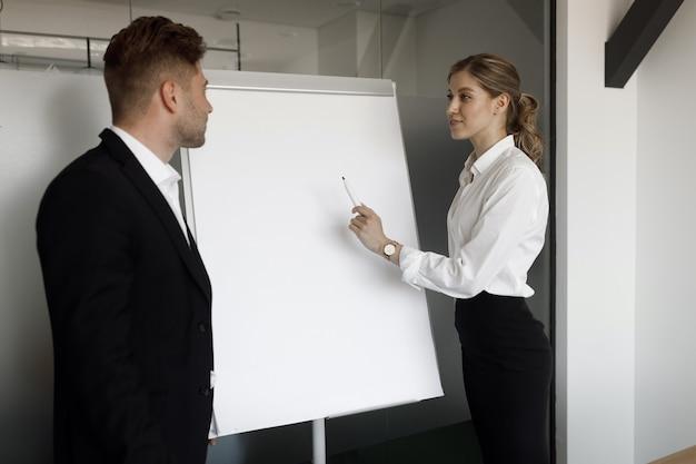 플립 차트에 몇 가지 작업을 하는 젊은 사업가의 초상화. 두 남녀가 플립차트에 서서 비즈니스 문제에 대해 토론합니다.
