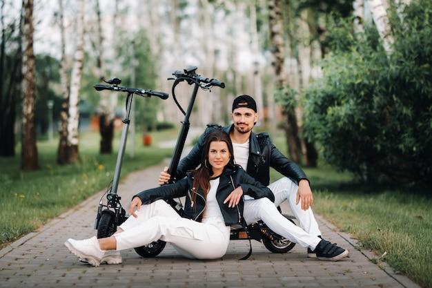 電動スクーターの近くに座って、一緒に自然の中で時間を楽しんでいるカップルの肖像画、電動スクーターの2人の恋人。スクーターの人々。