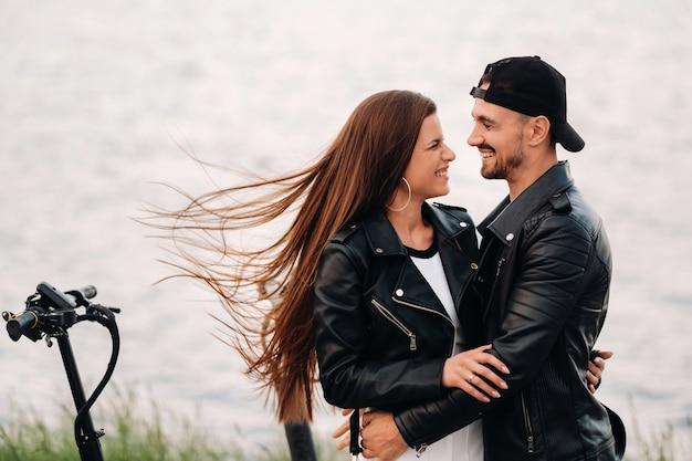 電動スクーターの近くに座って、一緒に自然の中で時間を楽しんでいるカップルの肖像画、電動スクーターの2人の恋人