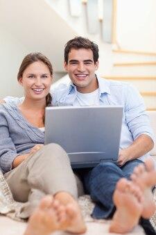 彼らはリビングルームにソファの上に横たわってノートを使用してカップルの肖像画