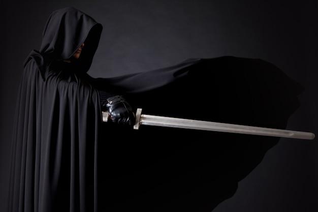 Портрет отважного воина-странника в черном плаще с мечом в руке.