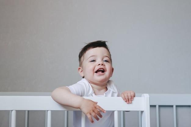 침실에 있는 침대에 흰색 바디수트를 입은 크롤링 및 smilling 소년 아기의 초상화. 파란색 큰 눈. copyspace 측면 보기와 함께 행복 한 어린 시절 개념