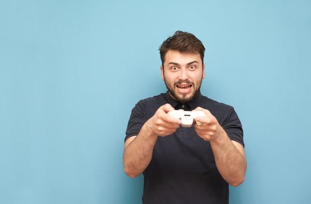 Портрет сумасшедшего взрослого геймера с бородой играет в видеоигры, радуется победе на синем