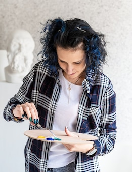 彼女のスタジオで作業しているパレットに油絵の具を置く創造的な女性アーティストの肖像画