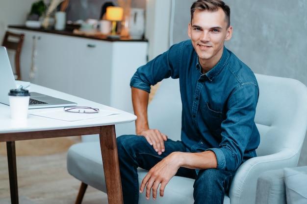 ホームオフィスに座っている創造的な若い男の肖像画。