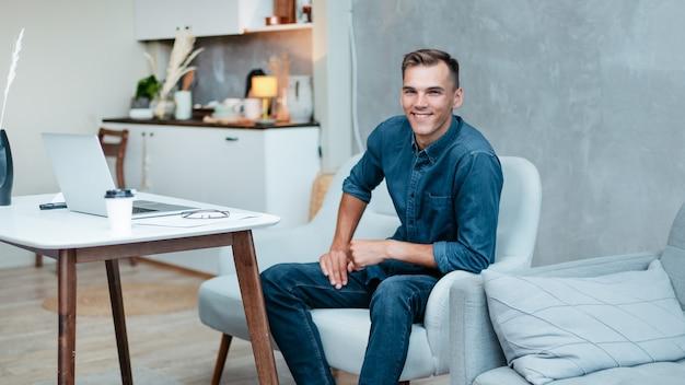 ホームオフィスに座っている創造的な若い男の肖像画