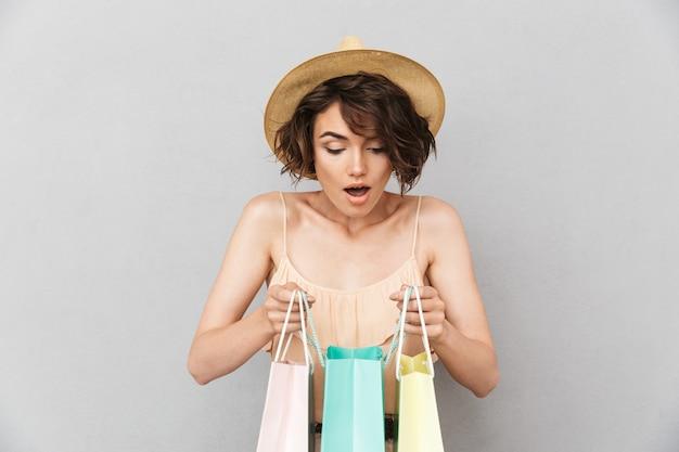 夏の帽子の好奇心旺盛な若い女性の肖像画
