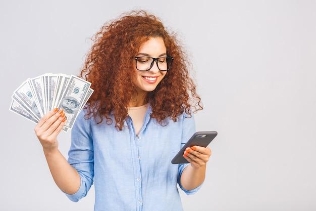 白い背景の上に孤立して立っている、お金の紙幣を保持している巻き毛の美しい少女の肖像画