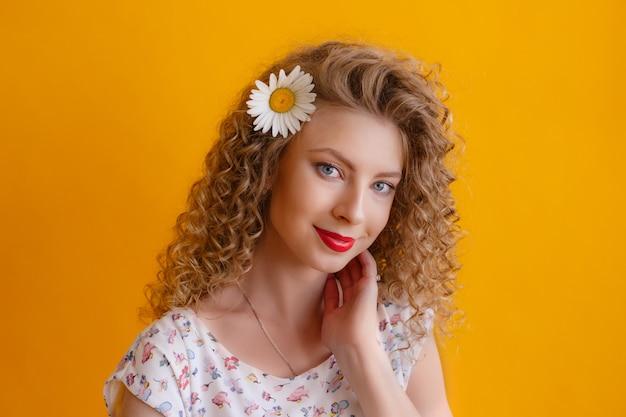 Портрет кудрявой девушки с ромашкой в волосах на желтом