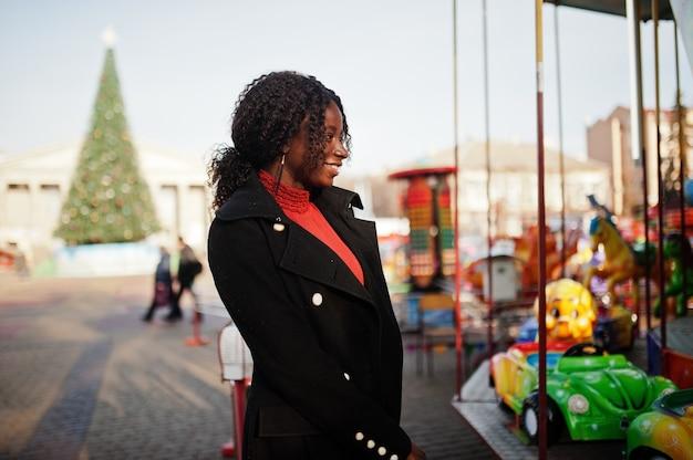 カルーセルに対してポーズをとるファッショナブルな黒いコートと赤いタートルネックを身に着けている巻き毛のアフリカの女性の肖像画。