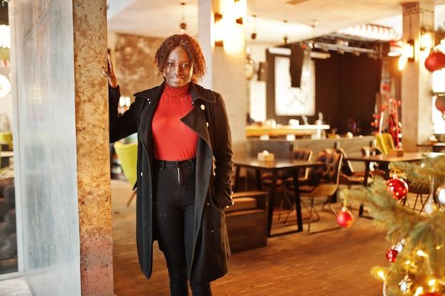 ファッショナブルな黒いコートと赤いタートルネックを身に着けている巻き毛のアフリカの女性の肖像画は、新年の木の装飾に対してポーズをとっています。