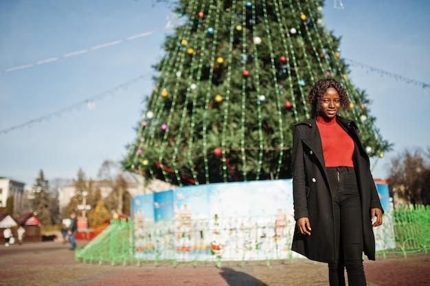 ファッショナブルな黒いコートと赤いタートルネックが街の主要な新年の木に対して屋外ポーズを身に着けている巻き毛のアフリカの女性の肖像画。