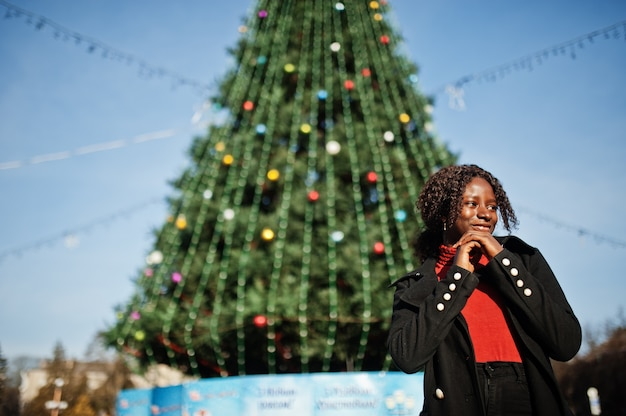 ファッショナブルな黒いコートと赤いタートルネックを身に着けている巻き毛のアフリカの女性の肖像画は、都市の主要な新年の木に対して屋外でポーズをとっています。