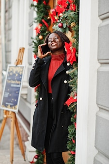クリスマスの装飾、大晦日、ドアの近くで屋外でポーズをとるファッショナブルな黒いコートと赤いタートルネックを身に着けている巻き毛のアフリカの女性の肖像画。電話で話します。