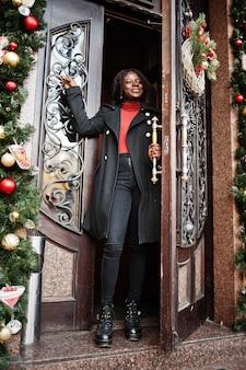 クリスマスの装飾、大晦日、ドアの近くで屋外でポーズをとるファッショナブルな黒いコートと赤いタートルネックを身に着けている巻き毛のアフリカの女性の肖像画。