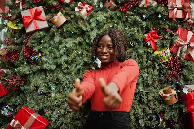 クリスマスの装飾、大晦日をテーマにポーズをとってファッショナブルな赤いタートルネックを身に着けている巻き毛のアフリカの女性の肖像画。親指を立てる。